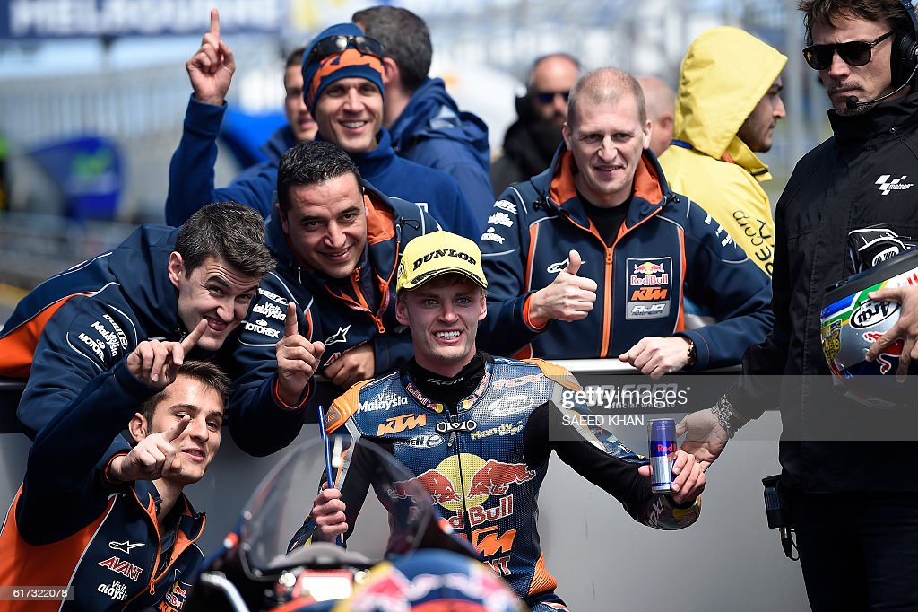 Red Bull KTM Ajo South African rider Brad Binder (C) celebrates his victory with teammates after the Australian Moto3 race at Phillip Island on October 23, 2016. / AFP / SAEED