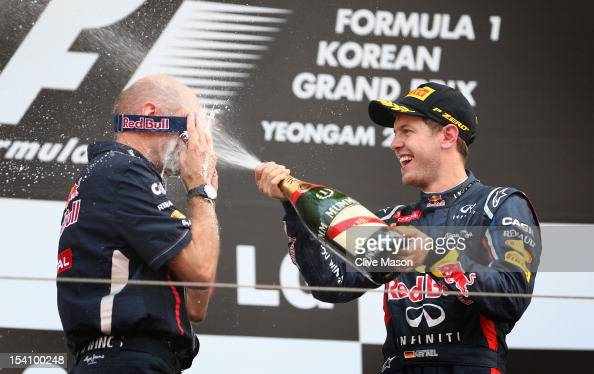 Red Bull Racing Chief Technical Officer Adrian Newey wears mechanics goggles to protect his eyes as race winner Sebastian Vettel of Germany and Red...