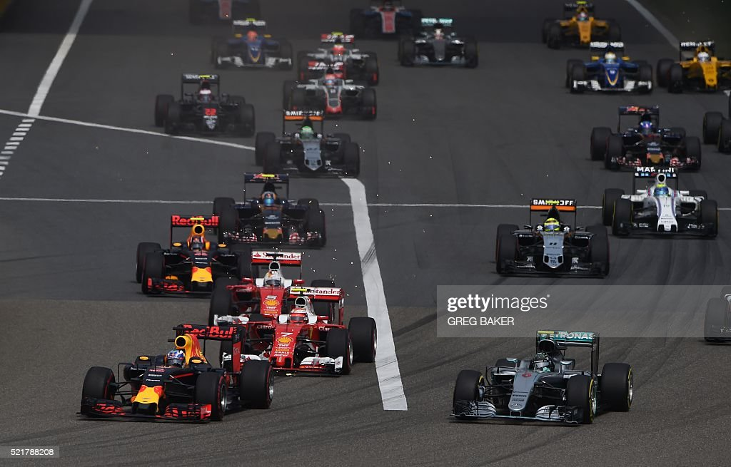 Red Bull Racing's Australian driver Daniel Ricciardo (front L) leads Mercedes AMG Petronas F1 Team's German driver Nico Rosberg (front R) into the first corner at the start of the Formula One Chinese Grand Prix in Shanghai on April 17, 2016. / AFP / GREG