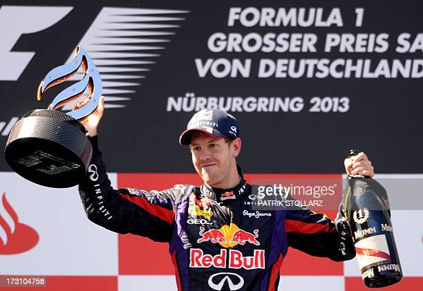 Red Bull Racing's German driver Sebastian Vettel celebrates on the podium at the Nurburgring race track on July 7 2013 in Nuerburg after the German...