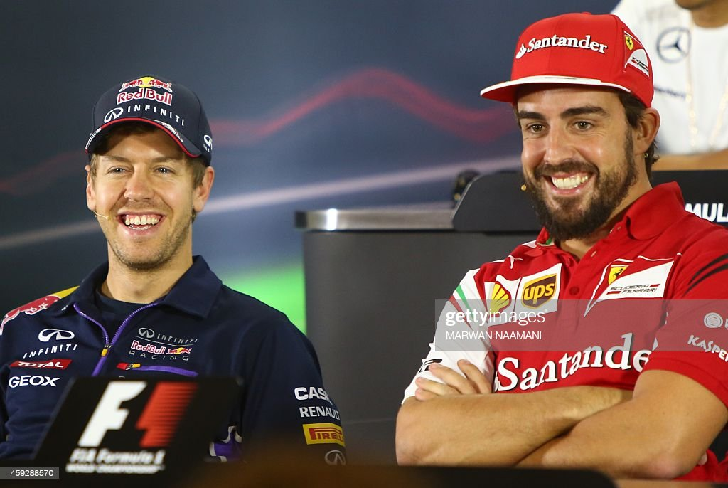 Red Bull Racing's German driver Sebastian Vettel chats with Ferrari's Spanish driver Fernando Alonso during the press conference at the Yas Marina...