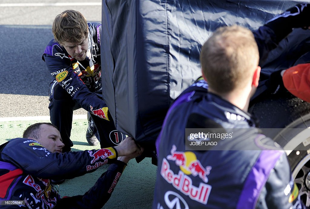 Red Bull Racing's German driver Sebastian Vettel (L) helps his mechanics to cover his car after it broke down during the second day of Formula One testing at the Catalunya racetrack in Montmelo, near Barcelona, on February 20, 2013. AFP PHOTO / JOSEP LAGO