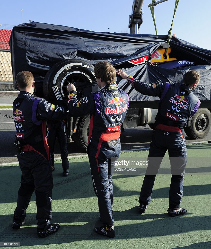 Red Bull Racing's German driver Sebastian Vettel (C) helps mechanics as his car is towed after breaking down during the second day of Formula One testing at the Catalunya racetrack in Montmelo, near Barcelona, on February 20, 2013.