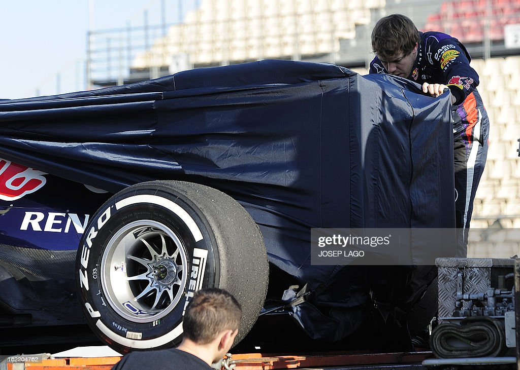 Red Bull Racing's German driver Sebastian Vettel helps mechanics to cover his car after it broke down during the second day of Formula One testing at the Catalunya racetrack in Montmelo, near Barcelona, on February 20, 2013. AFP PHOTO / JOSEP LAGO
