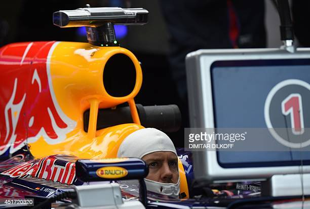 Red Bull Racing's German driver Sebastian Vettel looks at a control screen in the pits during the third practice session at the Silverstone circuit...
