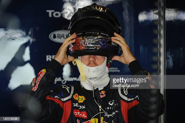 Red Bull Racing's German driver Sebastian Vettel removes his helmet in the pits at the Yas Marina circuit on November 11 2011 in Abu Dhabi during the...
