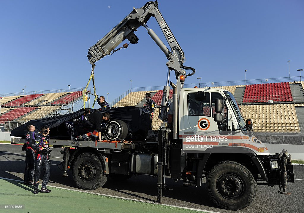 Red Bull Racing's German driver Sebastian Vettel (C) stands on a tow truck as mechanics cover his car after it broke down during the second day of Formula One testing at the Catalunya racetrack in Montmelo, near Barcelona, on February 20, 2013. AFP PHOTO / JOSEP LAGO