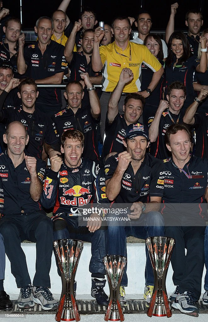 Red Bull-Renault driver Mark Webber of Australia (2nd R) and teammate Sebastian Vettel of Germany (2nd L), together with team principal Christian Horner (R) and technical director Adrian Newey (L), celebrate with team crew after winning the Formula One Indian Grand Prix 2012 at the Buddh International circuit in Greater Noida, on the outskirts of New Delhi on October 28, 2012.