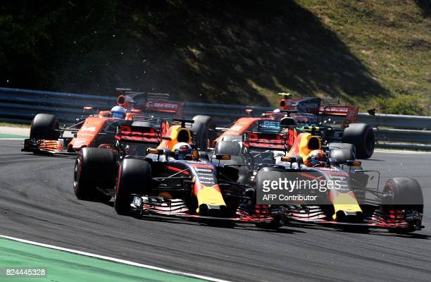 Red Bull's Australian driver Daniel Ricciardo and Red Bull's Dutch driver Max Verstappen collide as they race at the Hungaroring circuit in Budapest...