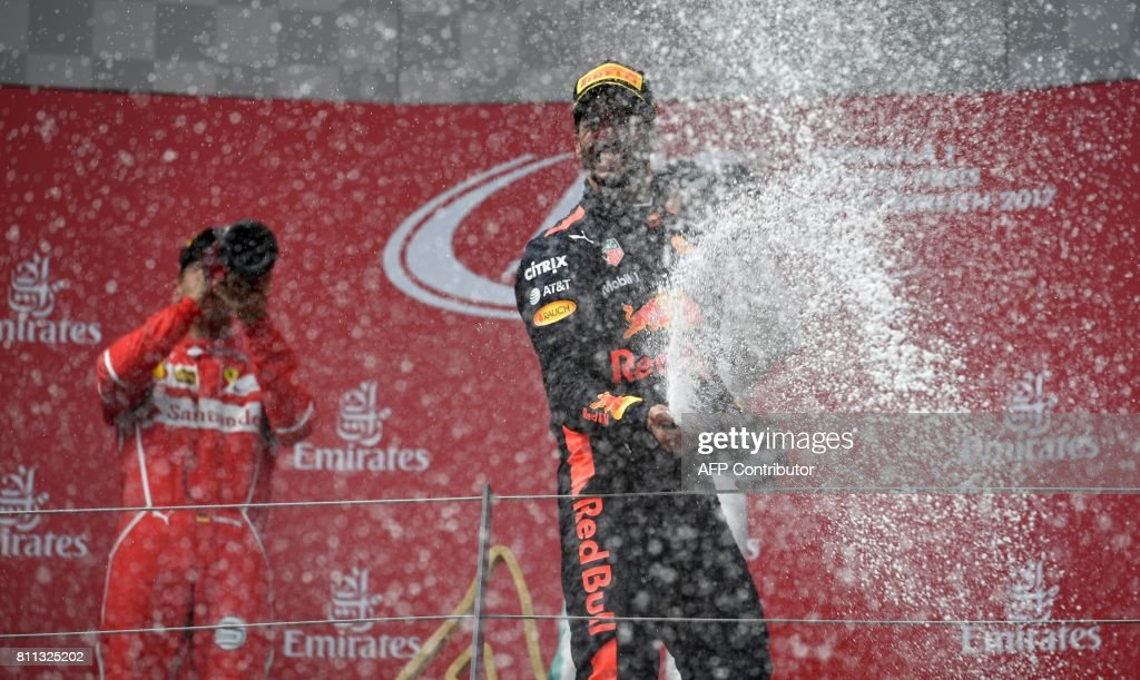 TOPSHOT - Red Bull's Australian driver Daniel Ricciardo (R) celebrates his third place on the podium after the Formula One Austria Grand Prix at the Red Bull Ring in Spielberg, on July 9, 2017. / AFP PHOTO / Andrej ISAKOVIC