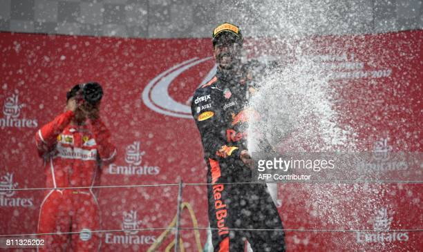 TOPSHOT Red Bull's Australian driver Daniel Ricciardo celebrates his third place on the podium after the Formula One Austria Grand Prix at the Red...
