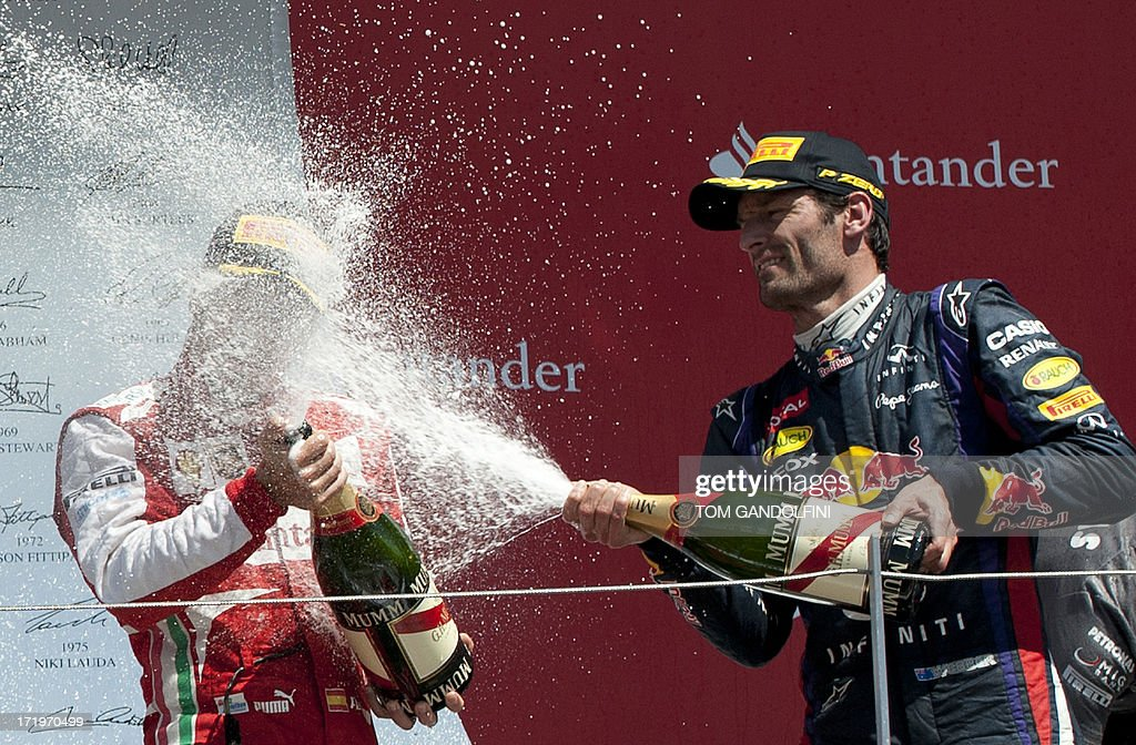 Red Bull's Australian driver Mark Webber (R) celebrates his second place by spraying champagne on the podium with third place, Ferrari's Spanish driver Fernando Alonso (L) at the Silverstone circuit in Silverstone on June 30, 2013 after the British Formula One Grand Prix.