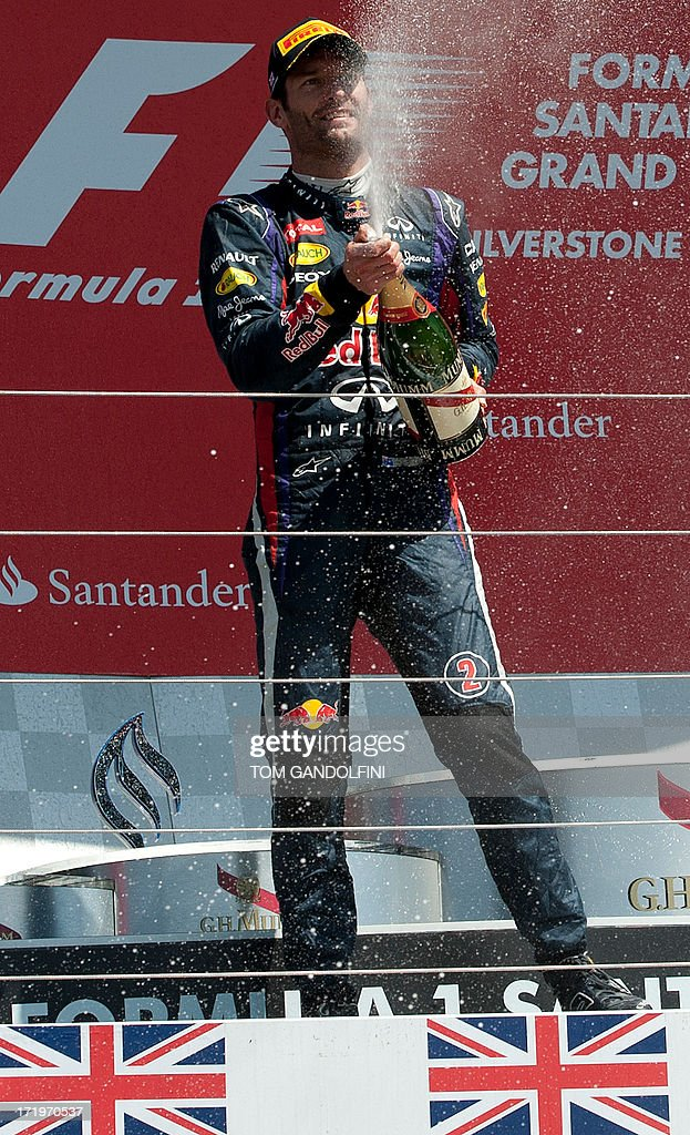 Red Bull's Australian driver Mark Webber celebrates his second place by spraying champagne on the podium at the Silverstone circuit in Silverstone on June 30, 2013 after the British Formula One Grand Prix. AFP PHOTO / TOM GANDOLFINI