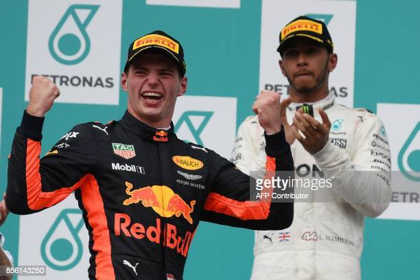 Red Bull's Dutch driver Max Verstappen celebrates on the podium after winning the Formula One Malaysia Grand Prix next to secondplaced Mercedes'...