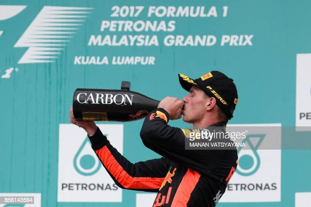 Red Bull's Dutch driver Max Verstappen celebrates on the podium after winning the Formula One Malaysia Grand Prix in Sepang on October 1 2017 / AFP...