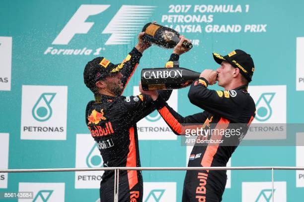 Red Bull's Dutch driver Max Verstappen celebrates on the podium after winning the Formula One Malaysia Grand Prix next to thirdplaced Red Bull's...
