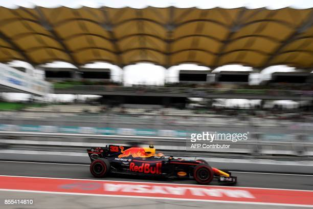 Red Bull's Dutch driver Max Verstappen drives in pit lane during the second practice session of the Formula One Malaysia Grand Prix in Sepang on...