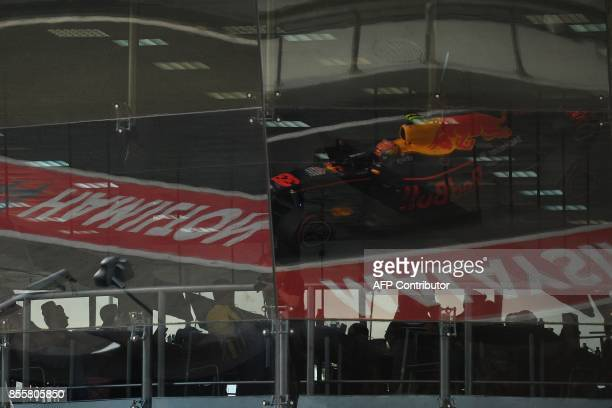 Red Bull's Dutch driver Max Verstappen is reflected in the glass windows as he drives into the pitlane during the qualifying session of the Formula...