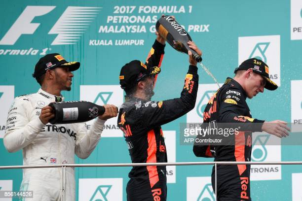 Red Bull's Dutch driver Max Verstappen is sprayed with champagne by thirdplaced Red Bull's Australian driver Daniel Ricciardo and secondplaced...