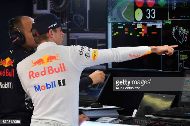 Red Bull's Dutch driver Max Verstappen looks at a screen in the pits during the Brazilian Formula One Grand Prix third practice session at the...