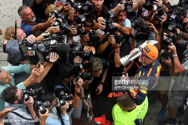 Red Bull's Dutch driver Max Verstappen poses for photograhers outside the team garage after winning the Formula One Malaysia Grand Prix in Sepang on...