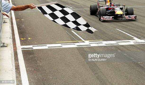 Red Bull's German driver Sebastian Vettel crosses the finish line of the Silverstone circuit on June 21 2009 in Silverstone during the British...