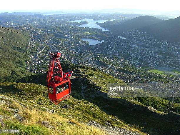 Red cable car traveling above landscape view of Bergen