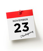 Red calendar pinned with a red push pin on white backgorund.  November 23 Thanksgiving writes on the calendar page. Vertical composition with copy space. November 23 Thanksgiving Concept.
