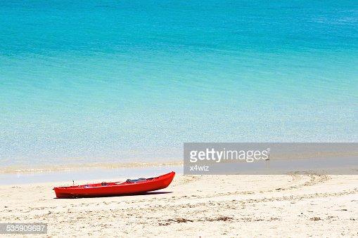 Rojo canoe on sandy beach : Foto de stock