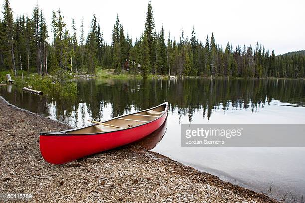 Red canoe on the shore of a lake.