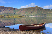A red canoe on the banks of Derwentwater.  In the background is Catbells a fell in the English Lake District National Park.