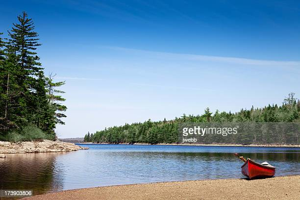 Red canoe stationed on a lake shore