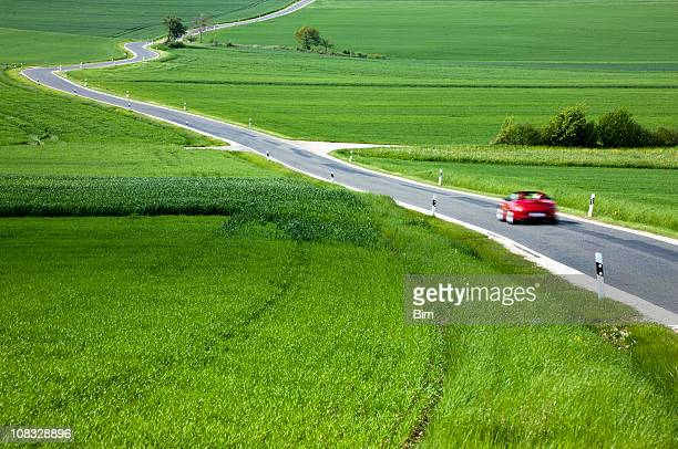 Red Car Driving Down Country Road in Spring Landscape