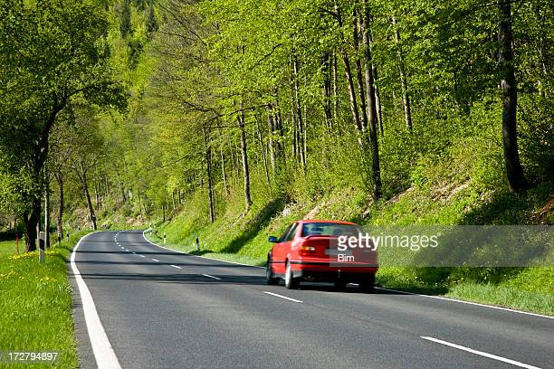 Red Car Driving on Country Road Through Forest in Spring