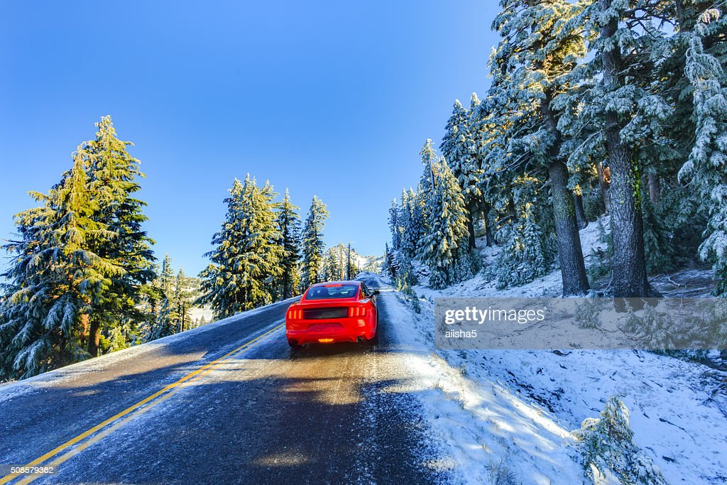 Red car on snowy and icy winter road : Stock Photo