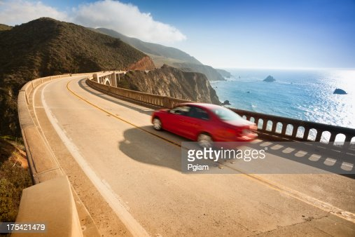 Red car zooms down Bixby Bridge in Big Sur