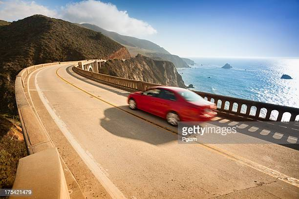 Red car zooms down Bixby Bridge in Big Sur