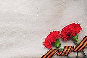 Red carnations and St. George ribbon on old paper background. Symbol may 9, victory day. Copy space.