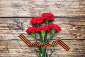 Red carnations and St. George ribbon on wooden background. Symbol may 9, victory day. Copy space