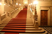 Red carpet cascading down a grand staircase