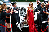 A stunning young starlet emerging from a limousine to fanfare and paparazzi demand on the red carpet