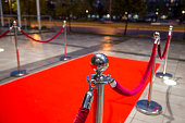 Red carpet between two rope barriers.