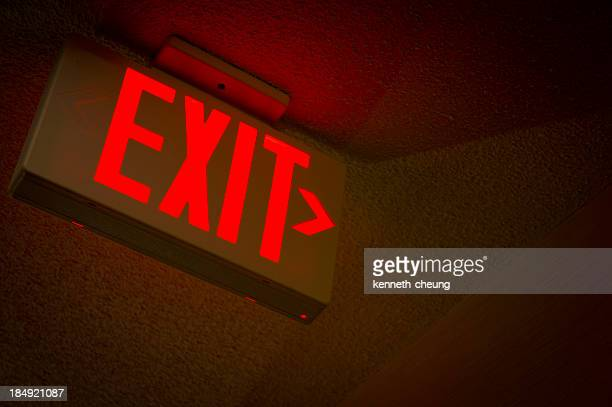 A red ceiling mounted EXIT sign