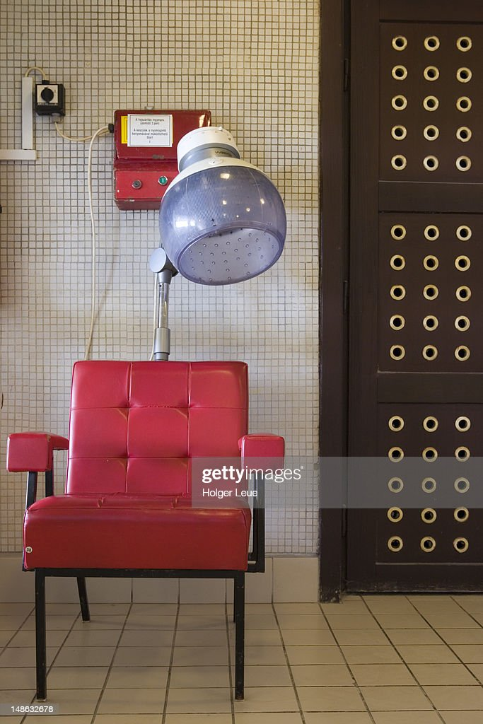 Red chair and coin-operated hair dryer at Gellert Baths. : Stock Photo
