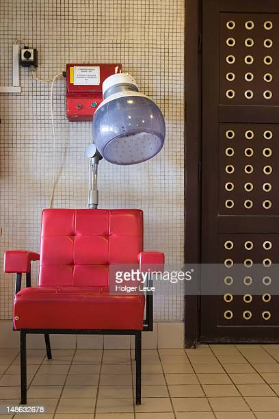 Red chair and coin-operated hair dryer at Gellert Baths.