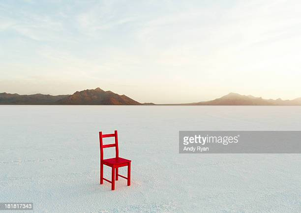 Red chair on salt flats, facing camera.