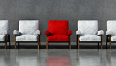 Red chair standing out among white chairs in a room.