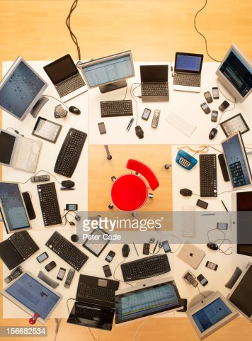 Red chair surrounded by desks covered in computers : Foto de stock