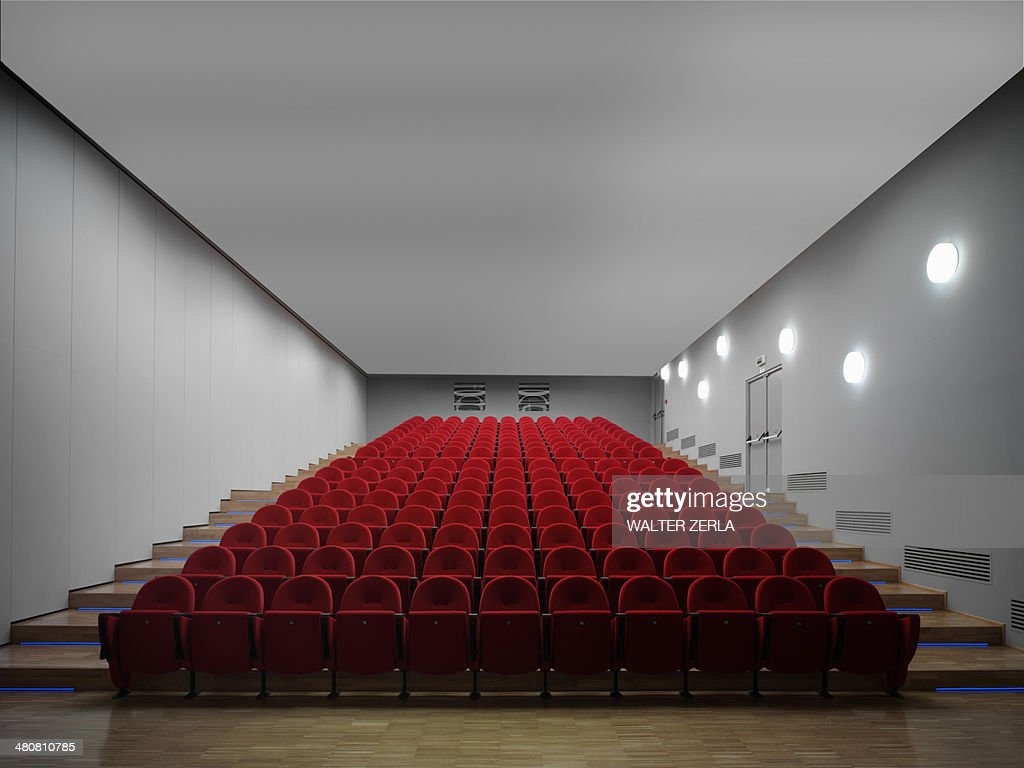 Red chairs in empty auditorium