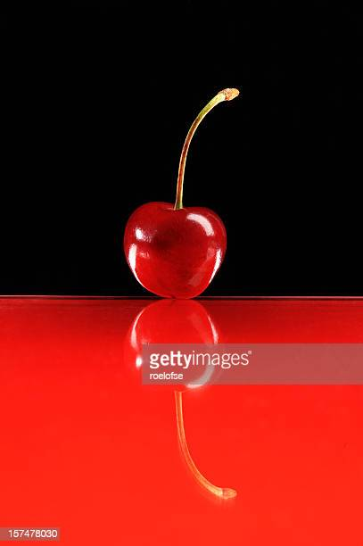 Red cherry on glass surface